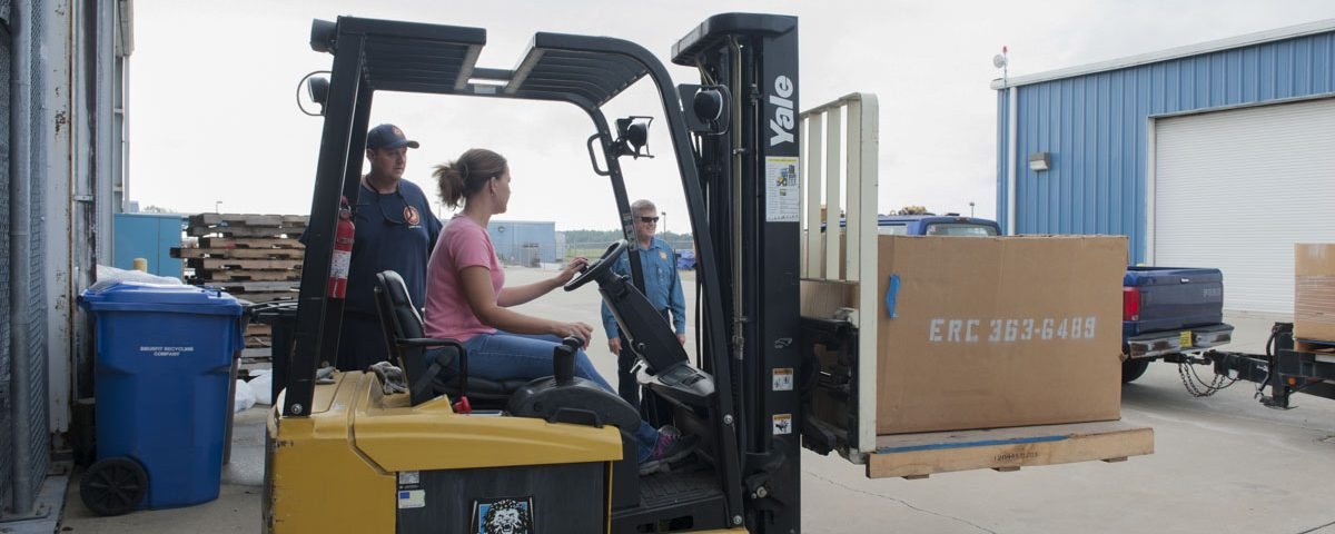 District staff driving a fork lift at district headquarters