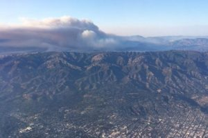 Aerial photo of mountain range with smoke plume in the background