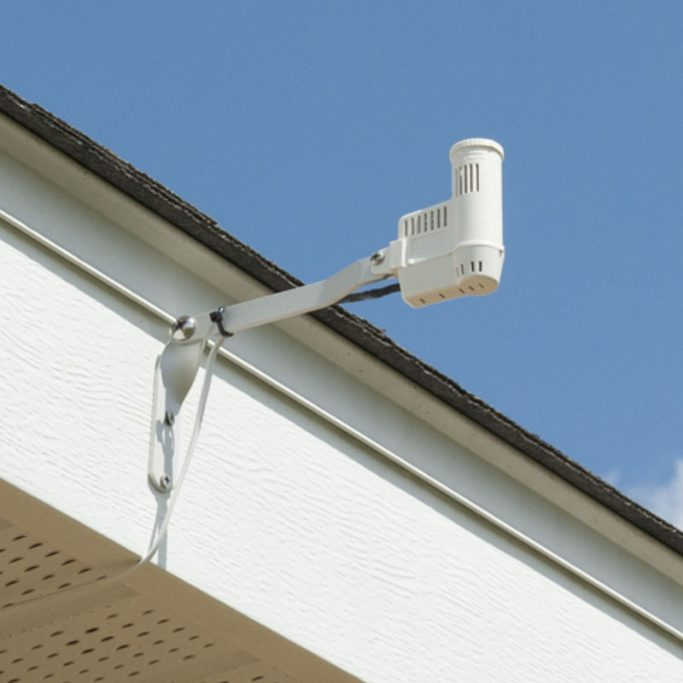 Irrigation rain sensor mounted to the eaves of a house