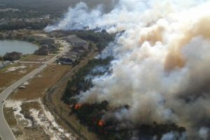 Aerial of a Prescribed fire burning near a neighborhood