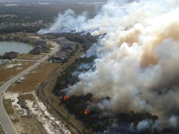 Aerial of a Prescribed fire burning near a neighborhood