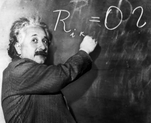 Albert Einstein writing on a chalk board