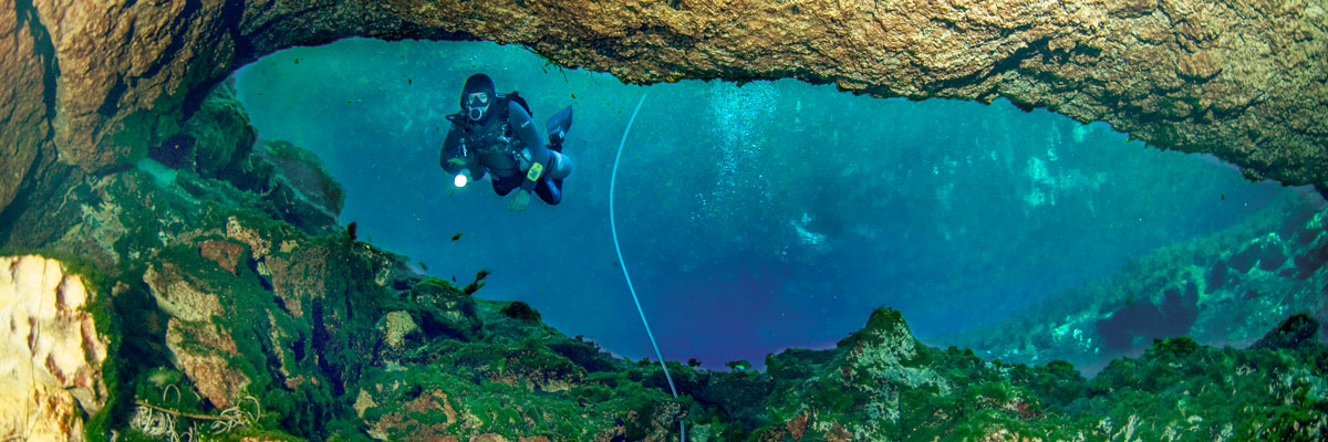 Scuba diver entering a cave