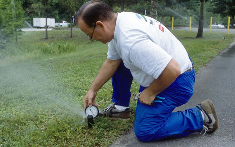 Man measuring the water pressure at an irrigation spray head