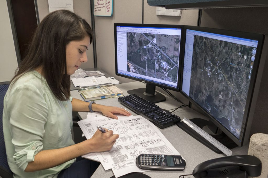 District staff engineer at their desk reviewing project plans