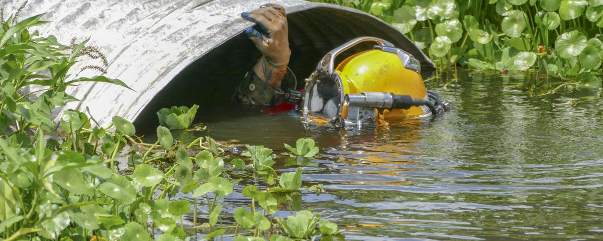 A diver inspecting a large culvert