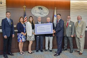 Jim Troiano and the City of Palm Coast Commissioners with a cost-share check