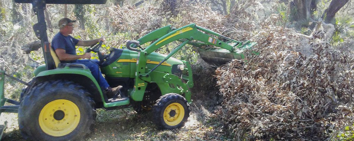 District staff using a frontloader to move tree debris