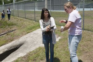 Students collecting water samples at a stormwater pond as part of the Blue School Grant program