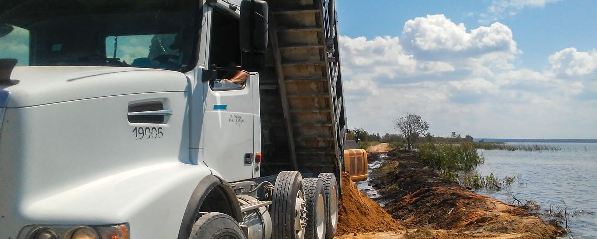 Dump truck delilvering fill material to a levee on Lake Apopka's north shore
