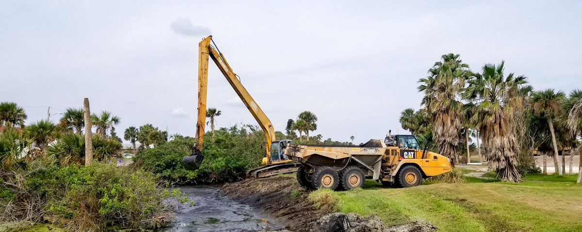 Backhoe expanding a stomwwater containment area on a golf course