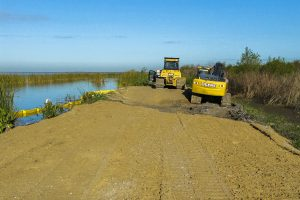 Tractors working to stabilize a levee along Lake Apopka