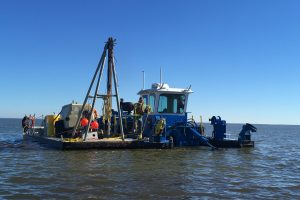 Perople working on a dredging barge on Lake Apopka