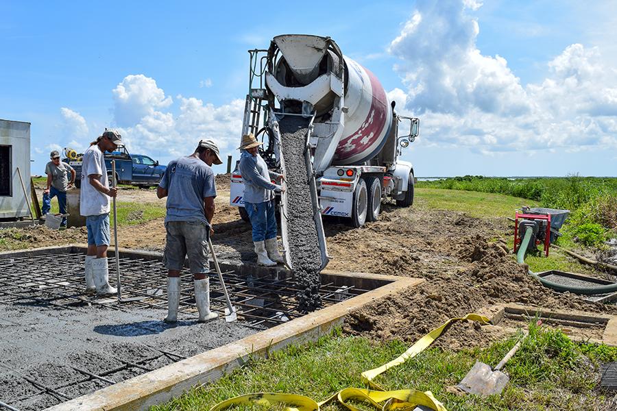 Construction crew pouring a concrete pad