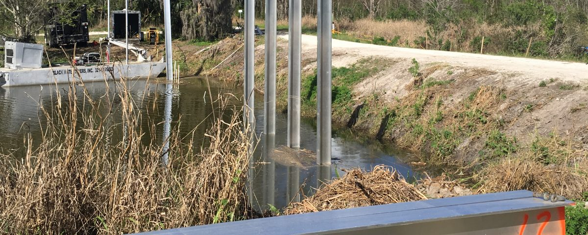 Levee cutting across a wetland with metal beams jutting out of the water