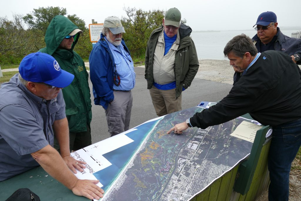 District staff review a map of the Mosquito Lagoon on a tour