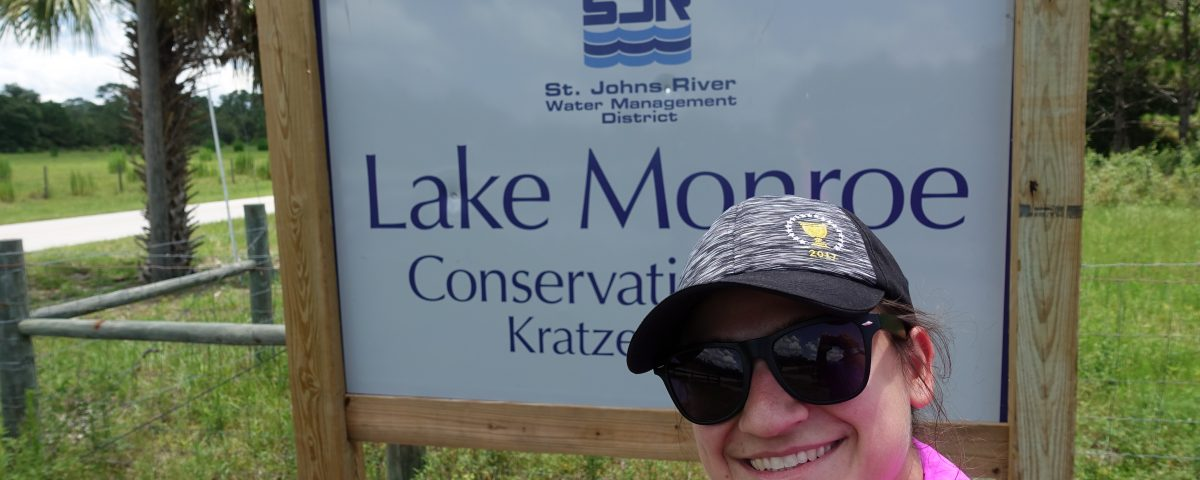 Selfie of a woman in front of the Lake Monroes Conservation Area entrance sign