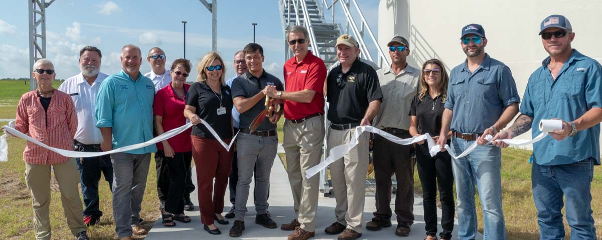 Lisa Kelley and shreholders cutting the ribbon at the Eustis Wastewater Treatment Plant Ribbon Cutting Event
