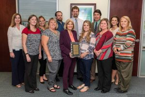 Finance staff with award