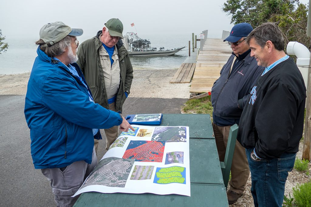 Men standing around table with maps at a boat ramp