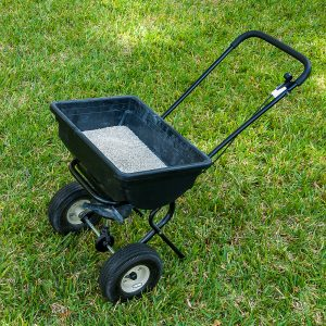 Lawn fertilizer spreader sitting on grass