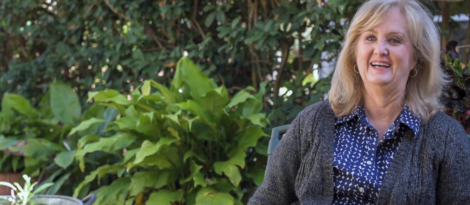 Deborah Weaver sitting in her garden