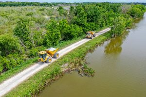Dump trucks driving on a levee along Lake Apopka