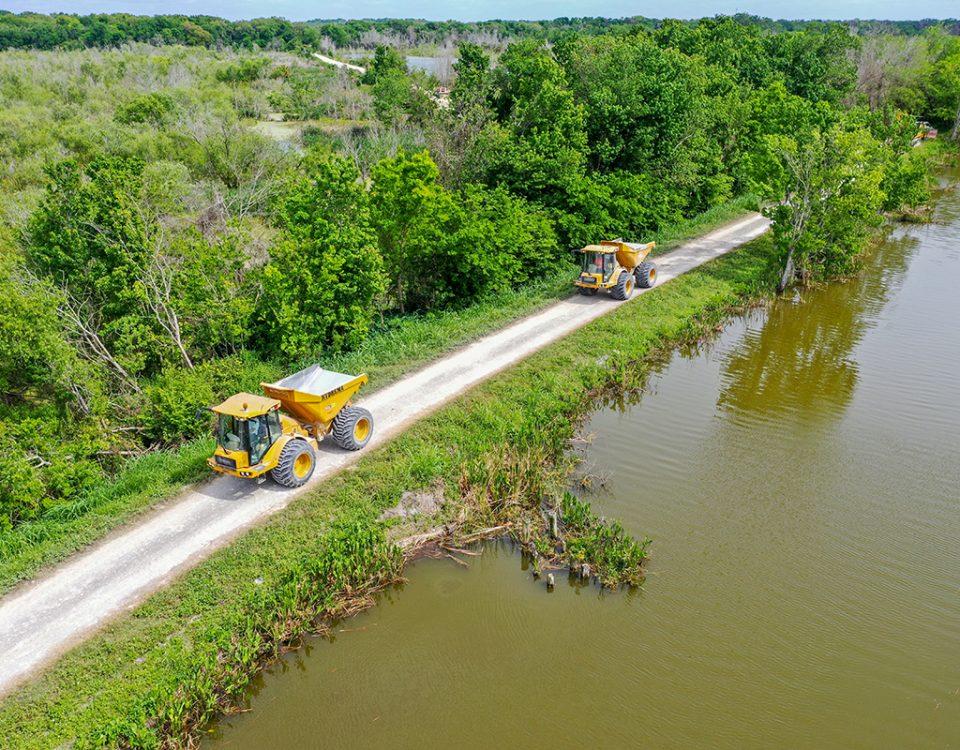 Dump trucks driving on a levee along Lake Apopka
