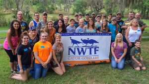 Group of people with a National Wild Turkey Federation banner