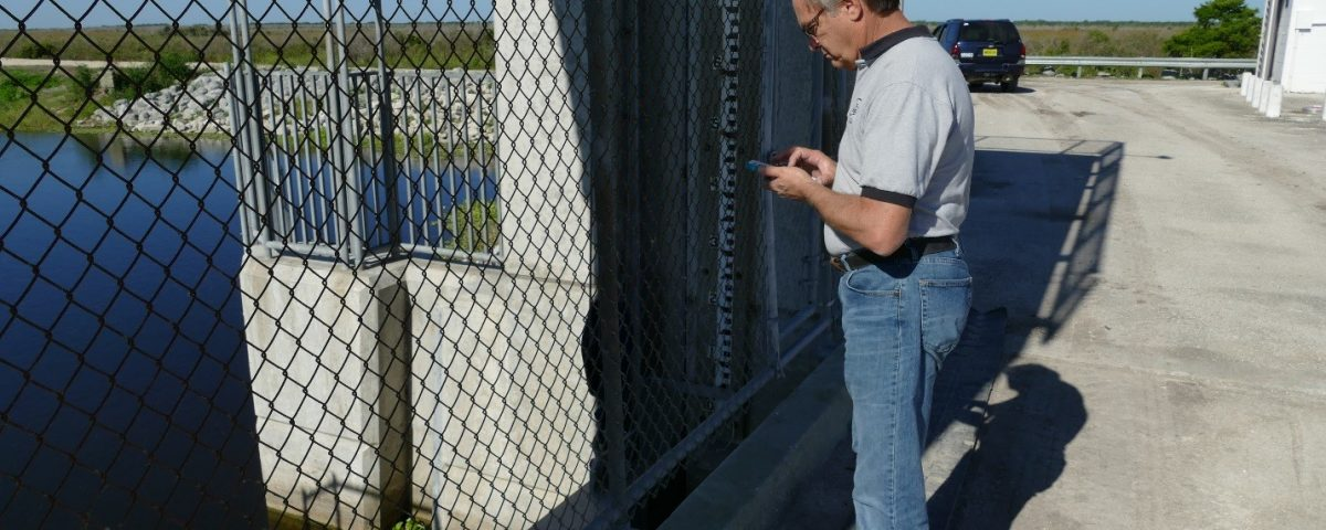 John Richmond using his cell phone to test a water control structure