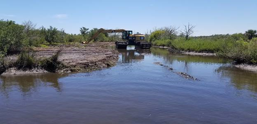 Excavator being operated by the site of a river