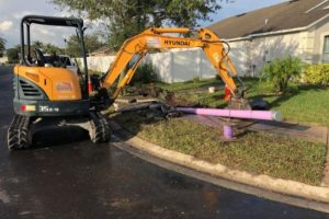 Excavator laying down purple pipes