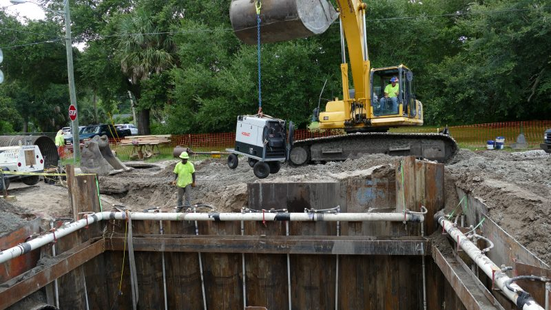 Excavator lowering equipment into a stormwater baffle box