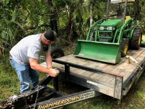 District staff member unloads a tractor from a trailer