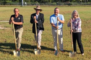 4 people with shovels standing in a field