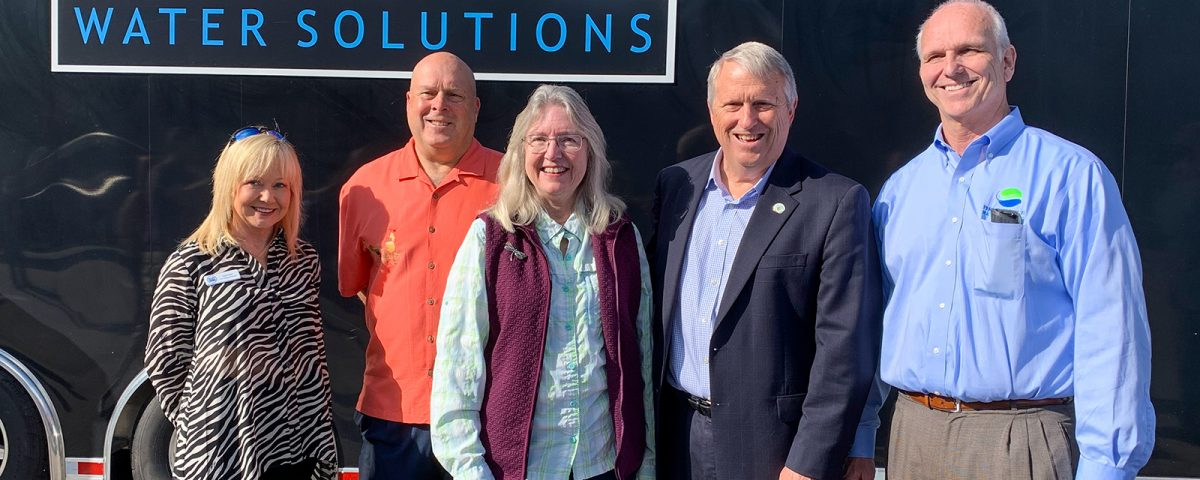 Five people standing infront of a trailer with a Phosphorus Free Water Solutions sign