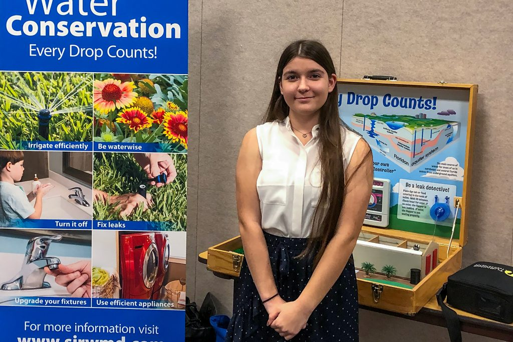 Madison Aprandini standing with a water conservation display