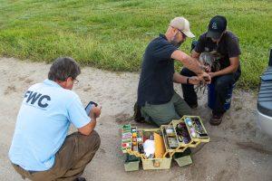 Tim Dellinger carefully fits a leg band on a Sandhill crane