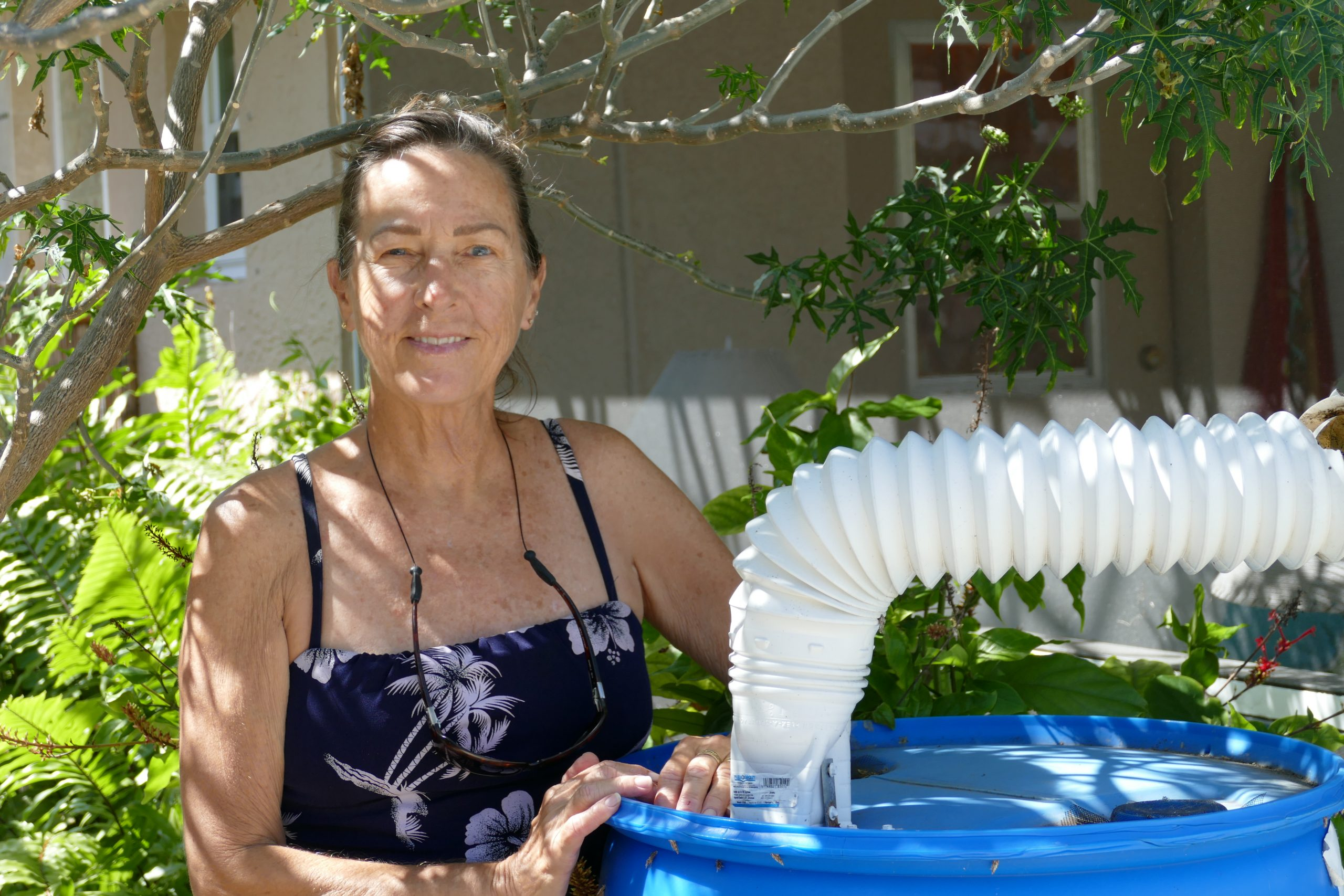 Abbey Calhoun reduces her household water bill by using a rain barrel to collect rainwater that she uses to water her garden.
