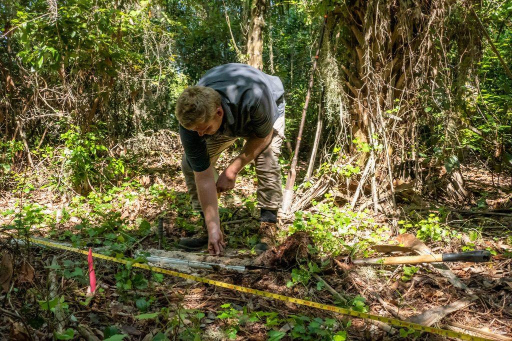 A District environmental scientist takes a soil sample