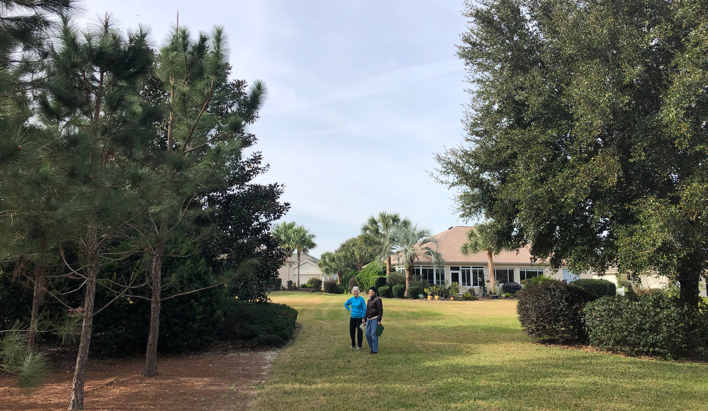 Two people standing in an open yard