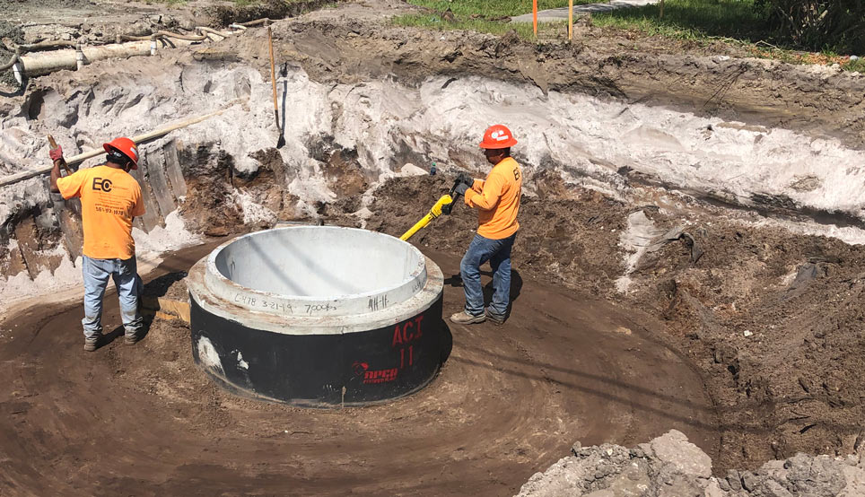 Construction workers installing sewer pipes