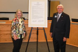 Dr. Ann Shortelle and Gen. Douglas Burnett standing next to a signed proclamation