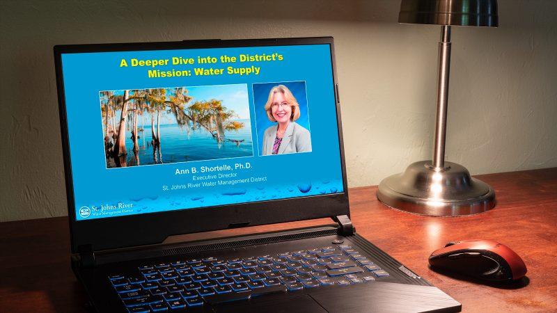 Computer on desk showing a webinar