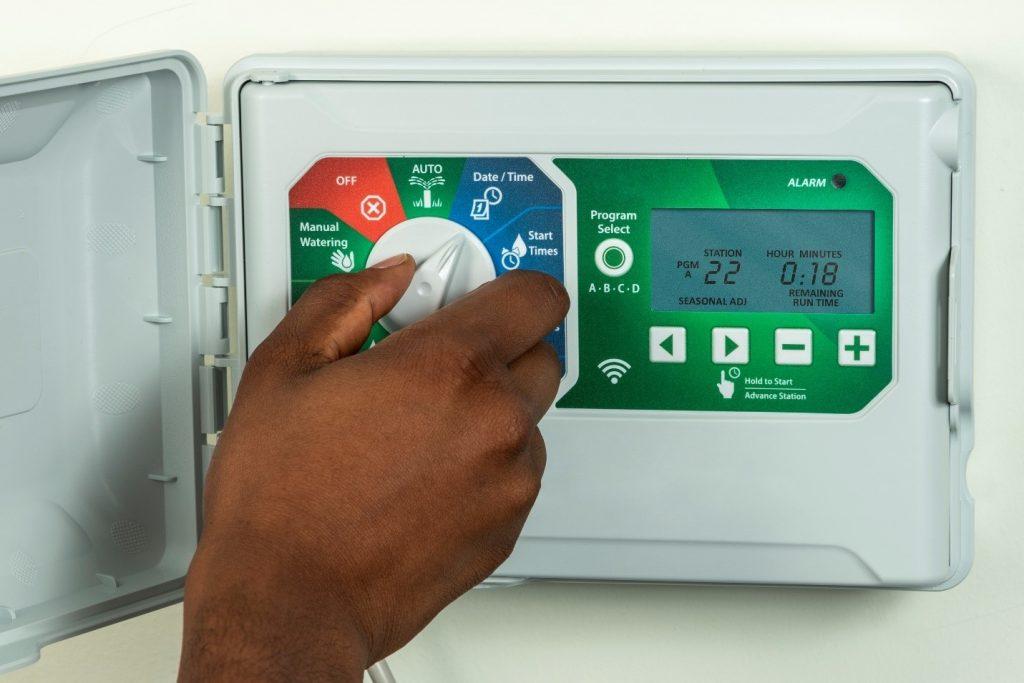 Person's hand adjusting a sprinkler system