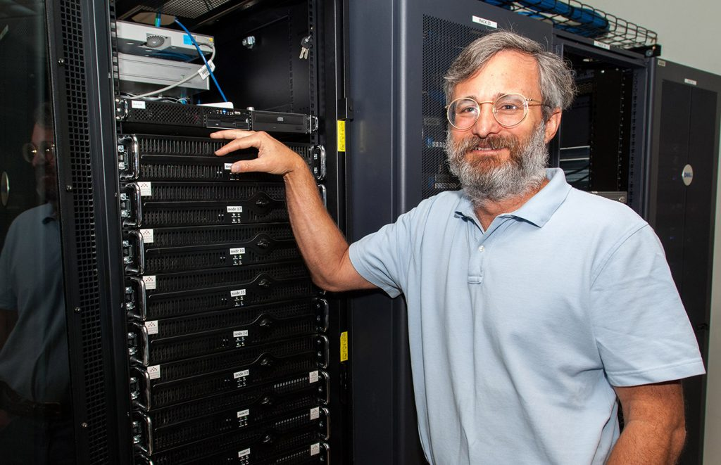 Dr. Peter Sucsy stands next to one of the computer clusters used in the district's modeling program