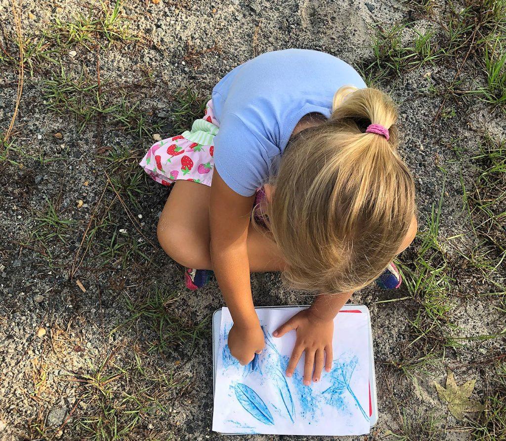Girl doing a leaf rub activity
