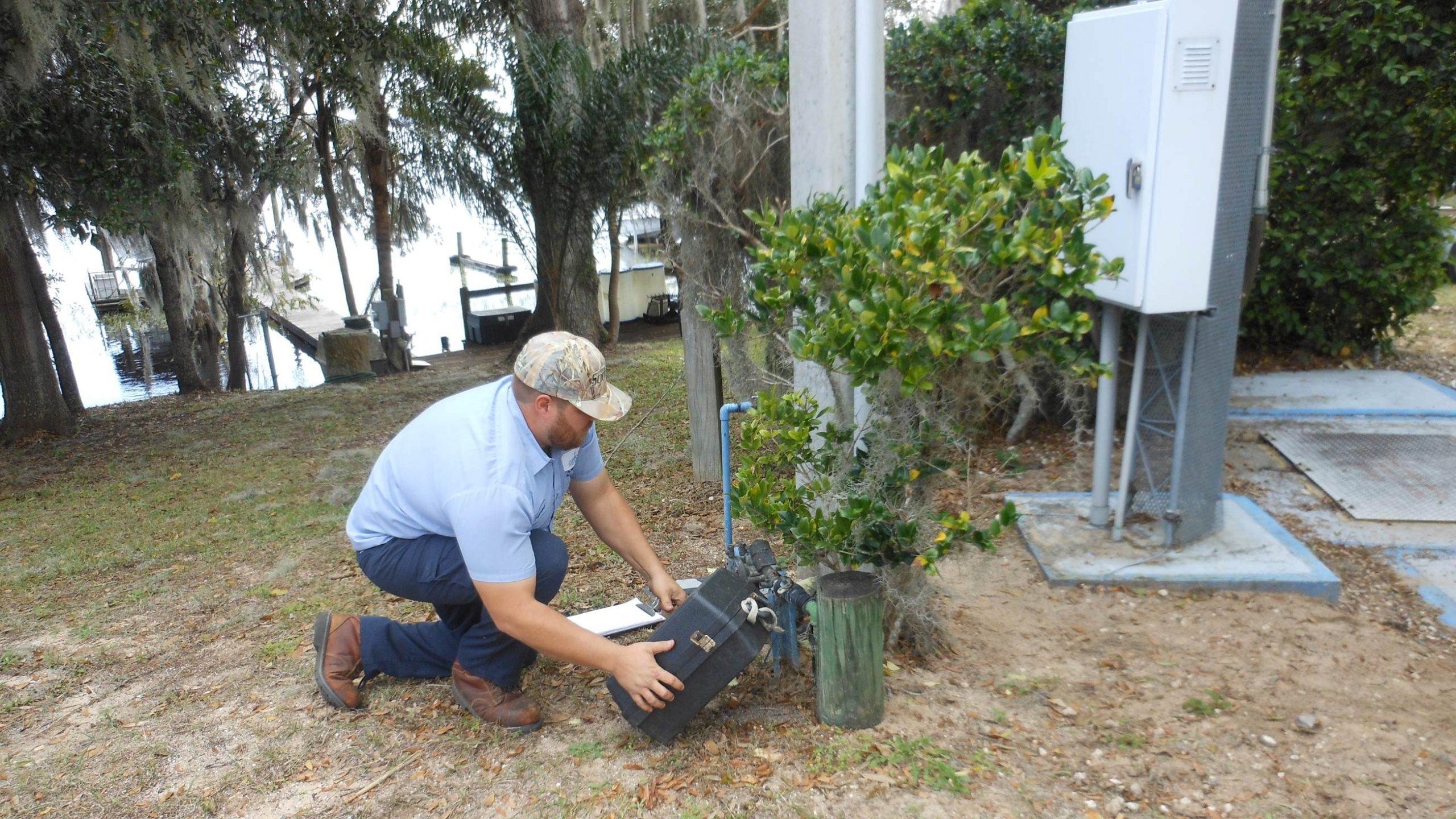 A Clermont Utilities worker repairs a homeowner's water meter.