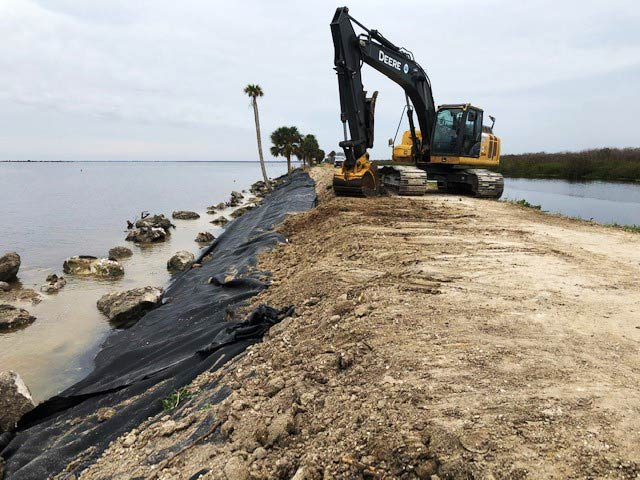 Excavator working on a water control levee