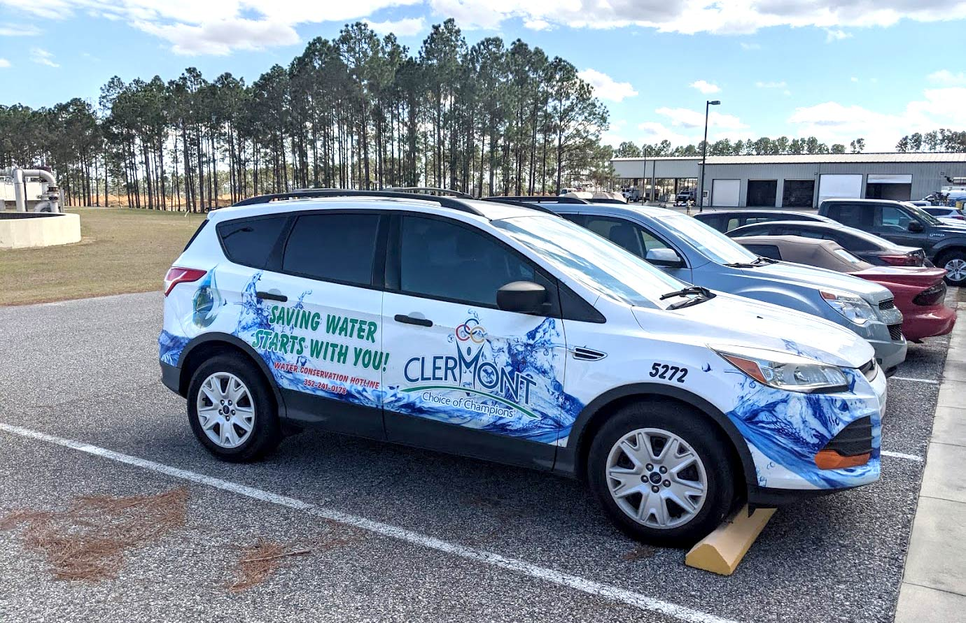 The Clermont Utilities vehicle with a colorful car wrap